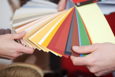 home improvement store: Man and woman discussing new paint colours comparing shades on a set of colour cards in a shop