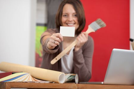 credentials: female interior designer showing white card in store Stock Photo