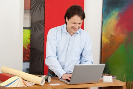 Attractive male decorator planning a house interior standing in his studio working on his laptop photo
