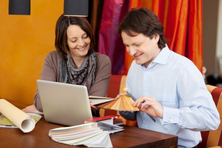 swatches: Interior designer in a client meeting sitting at a desk with an attractive woman showing her various samples