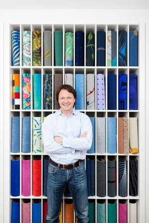 floor covering: Motivated attractive young salesman standing with his arms folded in front of a colourful carpet display in an interior decorating shop