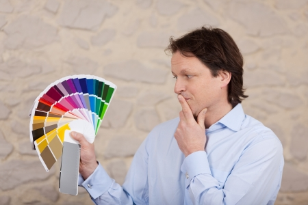 Man planning the colours of his new house standing with a confused thoughtful expression looking at a fanned set of colourful swatches in his hand photo