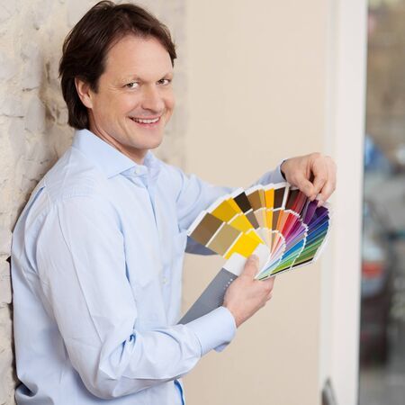 Smiling good looking man checking paint colours fort a wall against a colourful set of swatches held in his hand as he plans his renovations photo