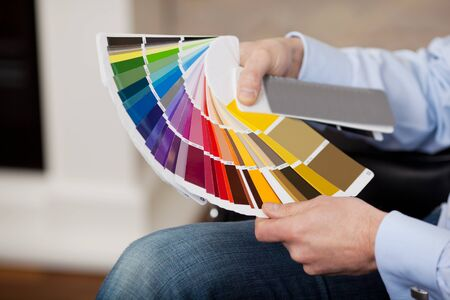 splayed: Man holding a set of paint colour swatches in all the colours of the spectrum splayed out in his hand as he tries to decide on a new colour for his house
