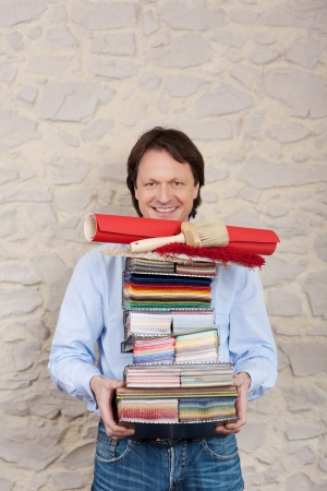 An interior decorating expert carries a high stack of paint, wallpaper and fabric samples in his arms, upper body smiling portrait against a wall with copyspace photo