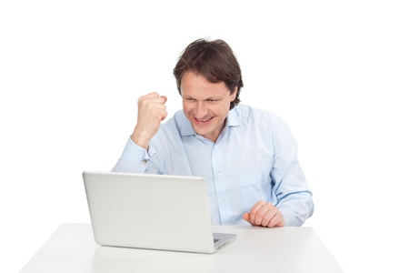 exultant: Exultant man balling his fist in glee as he reads good news on the screen of his laptop computer, over white Stock Photo