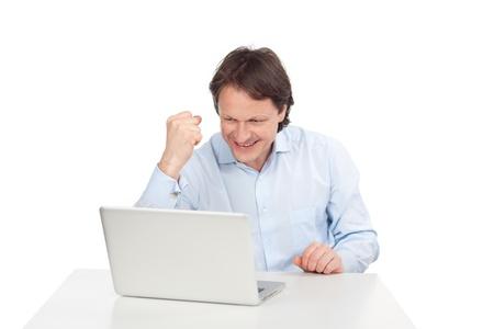 puños cerrados: Hombre exultante bolas puño de alegría al leer buenas noticias en la pantalla de su ordenador portátil, en blanco Foto de archivo