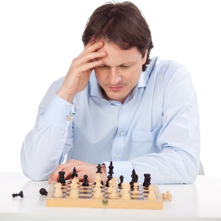 chess player: Man is concentrated over his chess board Stock Photo