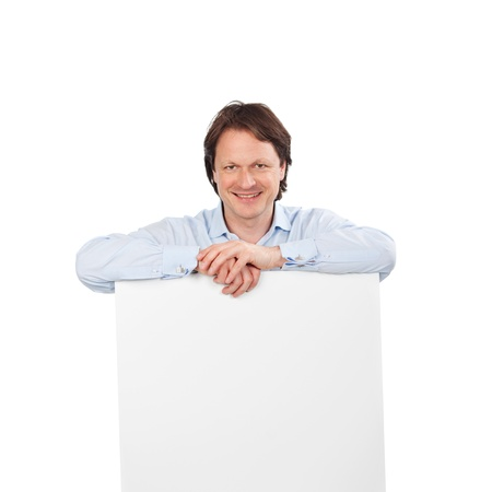 shirtsleeves: Smiling handsome man with a blank sign board leaning on the top in his shirtsleeves, copyspace for your text or advertisement