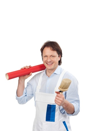 Friendly handyman in white overalls carrying a brush and wallpaper in his hands, isolated on white photo