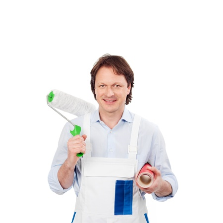 Friendly young male painter wearing white overalls with a roller and wallpaper in his hands, isolated on white photo