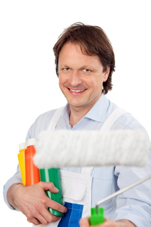 Competent painter with a roller and holding containers of colourful paint in his arms smiling at the camera isolated on white photo