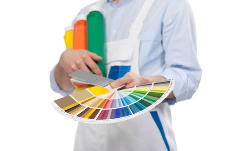 splayed: Handyman with paint colour cards in the colours of the rainbow held displayed in his hands, cropped view
