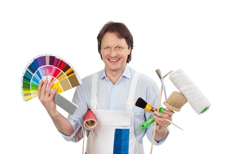 Confident handyman with samples displaying colour charts for paint while holding a roll of wallpaper and his tools in his hands photo