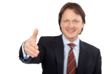 Confident businessman offering to shake hands conceptual of closing a business agreement a partnership, greeting or congratulations isolated on white photo