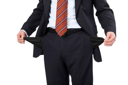 inside out: Man with empty pockets pulling them inside out to show his poverty isolated on white