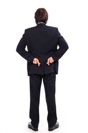 treacherous: Businessman standing full length crossing his fingers behind his back as he embarks on a shady deal or in a gesture of hope isolated on white