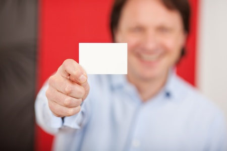 credentials: friendly smiling man in a shop showing white card