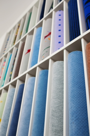 compartments: Low angle view of a range of coloured carpets for sale in a store or shop in a wall mounted display with individual compartments