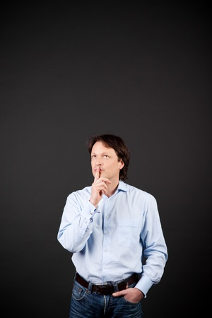 Thoughtful casual young man in jeans standing a dark studio background with copyspace with his hand to his chin photo