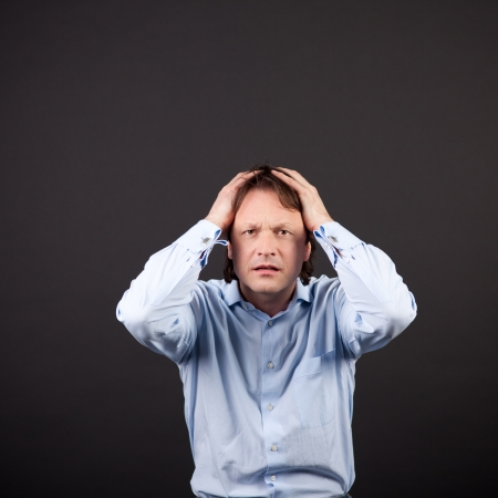 remorse: Crisis in the job as a young businessman reacts by holding his hands to his head with a look of desperation on a dark background Stock Photo