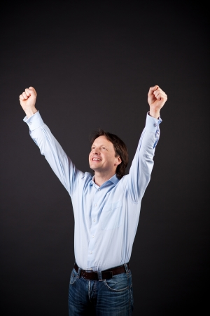 jubilation: Young man rejoicing raising his fists to the air in jubilation at a personal victory or success on a dark background