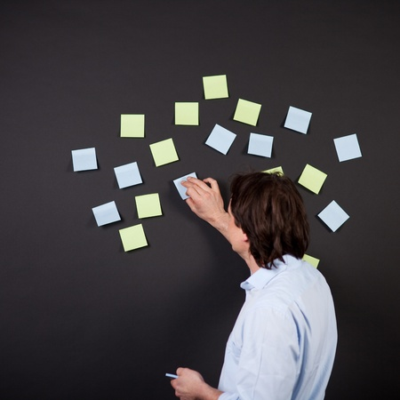 sticking to: mature man putting post-its on black wall Stock Photo
