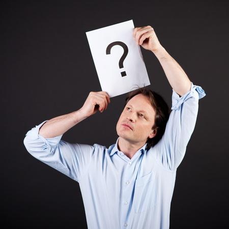 interrogativa: Hombre con un signo de interrogación dibujado en una hoja de papel que sostiene sobre su cabeza con una expresión pensativa en un fondo oscuro
