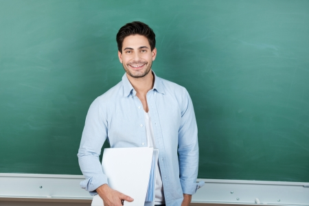 Portrait of confident male teacher holding binder against chalkboard in classroom photo