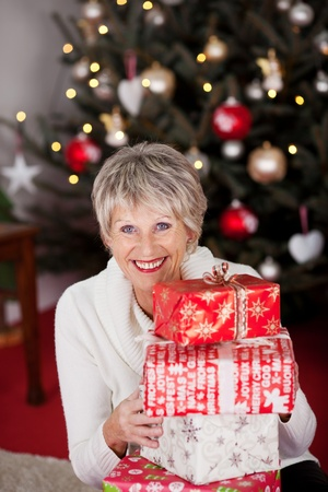 christmas shopping: High angle view of a beautiful vivacious happy grandmother with a stack of Christmas gifts sitting in front of a twinkling tree Stock Photo