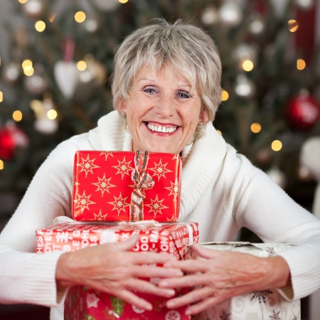 Laughing beautiful senior woman hugging a pile of Christmas gifts to her chest as she sits in front of a decorated Christmas tree photo
