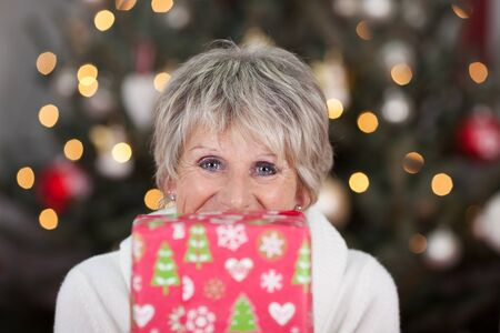 Happy senior woman with a Christmas gift in front of the lower half of her face looking at the camera with laughing eyes, Christmas tree backdrop with sparkling lights bokeh photo