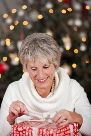 undoing: Beautiful stylish senior lady opening her Christmas gift in front of the sparkling Christmas tree carefully untying the bow Stock Photo