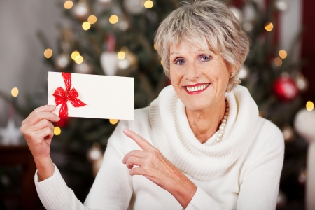 Smiling attractive senior woman pointing to a blank Christmas voucher in her hand as she sits in front of a decorated Christmas tree with lights photo