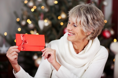 christmas bonus: Smiling stylish elderly woman displaying a red Christmas voucher in her hands in front of a twinkling Christmas tree