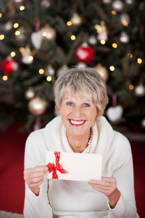 Smiling beautiful senior lady with a gift voucher displayed in her hands sitting in front of a decorated Christmas tree with twinkling lights Stock Photo - 20771752