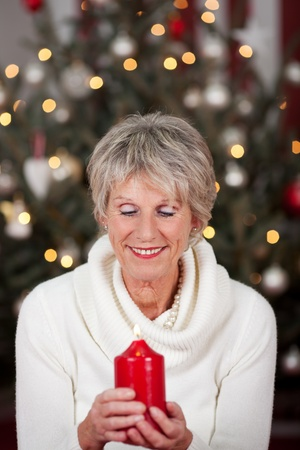 Serene beautiful elderly lady with a burning red Christmas candle held in her hands in front of a Christmas tree with a twinkling bokeh of lights Stock Photo - 20771703