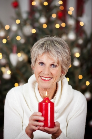 Happy senior woman with a large red burning candle cradled in her hands as she celebrates Christmas in front of her tree Stock Photo - 20771894