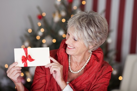 Glamorous retired lady with a christmas gift voucher displaying the blank white envelope with a red ribbon in front of the decorated tree, red and white themed Stock Photo - 20771837