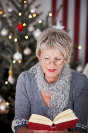 Attractive stylish elderly lady reading a book at Christmas sitting in front of the decorated Christmas tree in her living room Stock Photo - 20771668