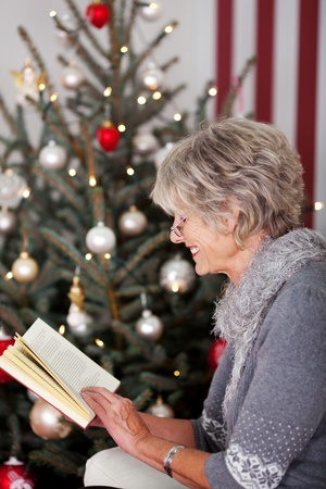 Stylish modern senior woman reading a book in front of a decorated Christmas tree Stock Photo - 20771867