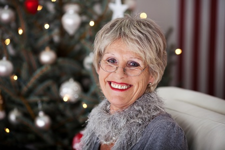 vivacious: Beautiful vivacious smiling senior woman sitting on a comfortable sofa in front of the Christmas tree