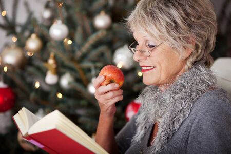Beautiful senior woman relaxing on a sofa in front of the family Christmas tree with a book and apple photo
