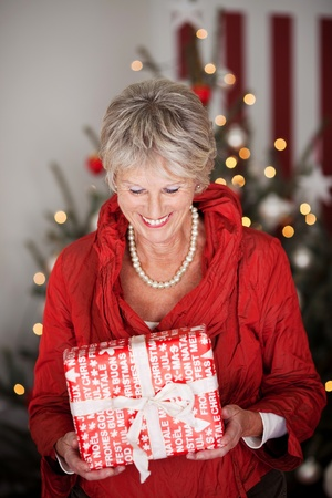 Happy beautiful senior woman smiling as she looks down at a Christmas gift she is holding in her hands Stock Photo - 20771734