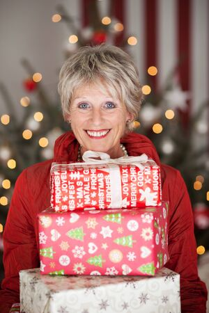 senior living: Happy smiling beautiful senior lady with a stack of Christmas gifts sitting in front of a decorated Christmas tree with a bokeh of twinkling lights Stock Photo