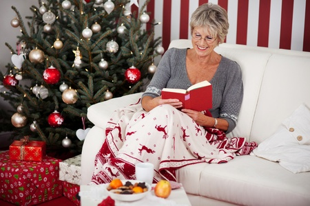 woman relaxing: Elderly attractive woman relaxing under a colourful blanket with reindeer on the sofa reading a book in front of the Christmas tree Stock Photo