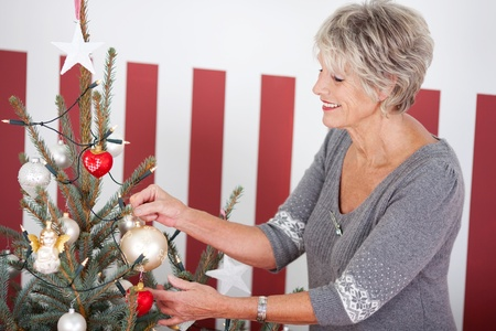 Attractive smiling senior woman hanging Christmas decorations on the branches of a Christmas tree, red and white themed with striped wallpaper background Stock Photo - 20785964