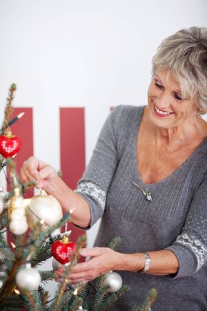 Beautiful senior woman with a lovely smile decorating a red and white themed Christmas tree with baubles and ornaments photo