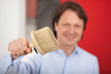 Smiling male decorator with a paint brush held in his hand with selective focus to the brush photo