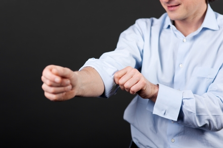 shirt sleeves: Closeup view of a man rolling up his shirtsleeves against a dark background